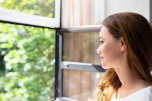 žena hľadá vokne čerstvý vzduch